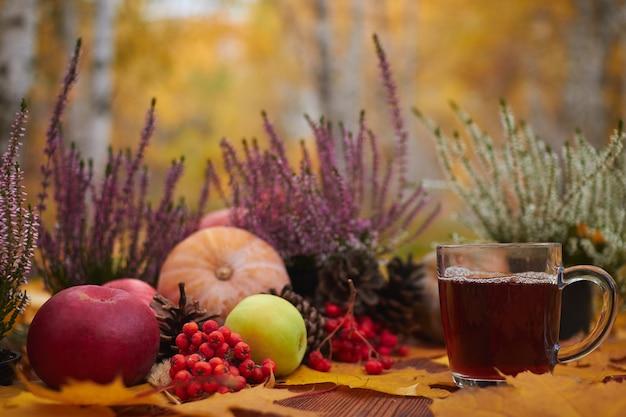 秋のベリーと野菜と木製のテーブルの上のお茶のカップ