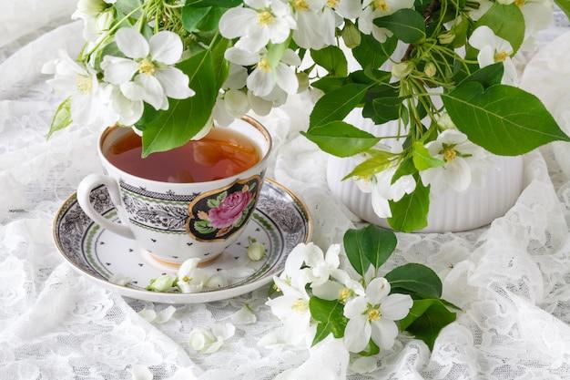 Чашка чаю на деревянном столе и цветении яблока. концепция время чая. завтрак чайная чашка подается с цветами.