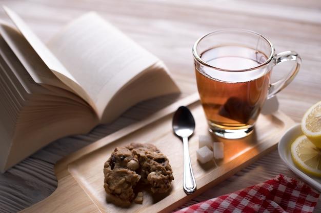 居心地の良い、リラックスした、平和な雰囲気の中で開かれた本とクッキーとレモンスライスの木製トレイ上のお茶
