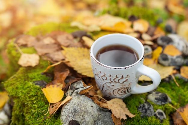 黄色の葉にお茶のカップ。秋の森を歩く