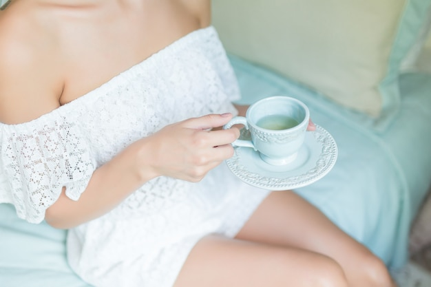 女性の手でお茶やコーヒーのカップは朝にクローズアップ