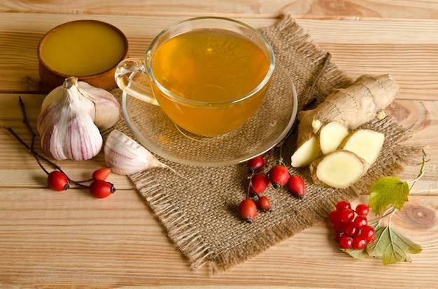木製のテーブルにお茶、生姜、蜂蜜、ローズヒップベリー、ガマズミ属の木のスライス
