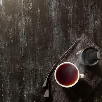 갈색 냅킨에 유용하고 따뜻한 차 한잔과 어두운 나무 테이블에 보온병