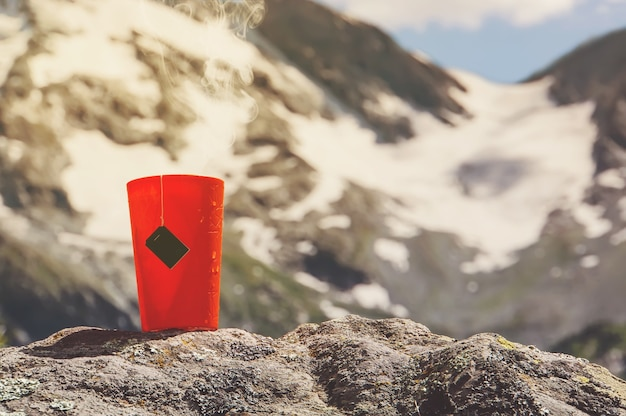 Чашка чая. теплый напиток в лесу. пикник в лесу. туризм и путешествия. кружка с заваренным чаем среди красивых озер и высоких гор