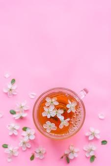 Чашка чая с цветками яблони. весенний розовый фон.