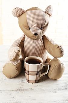 明るい表面のテーブルにクマとお茶のカップ