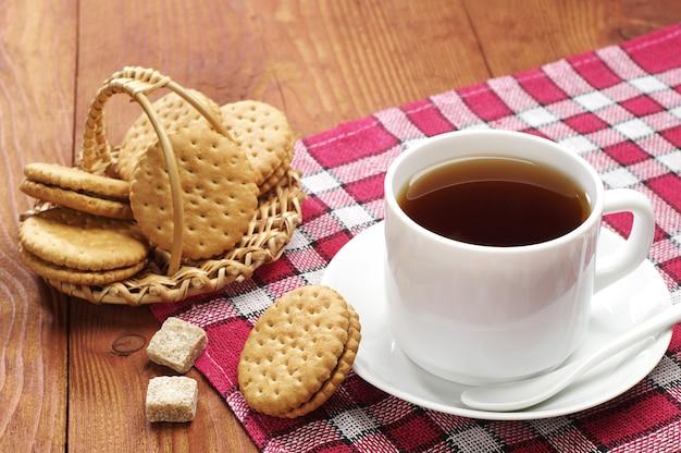 木製のテーブルにビスケットとお茶のカップ