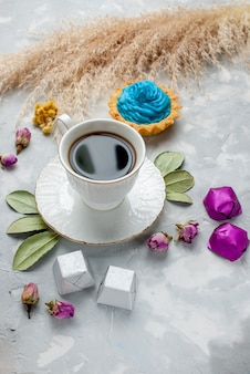 白灰色の机の上に青いクリームケーキチョコレートキャンディー、ビスケットスウィートティーキャンディーチョコレートとお茶のカップ