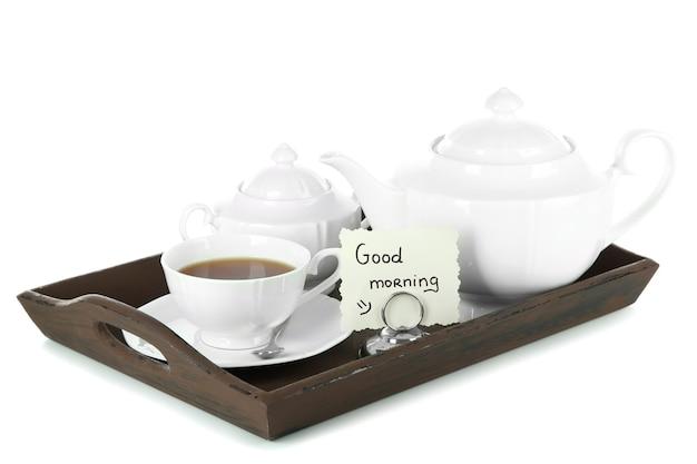 白で隔離される木製のトレイにケーキとお茶のカップ