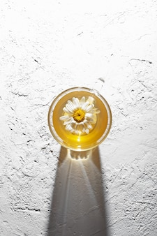 カモミールの花の上面図とお茶のカップ明るいテクスチャ背景シャドウコピースペース