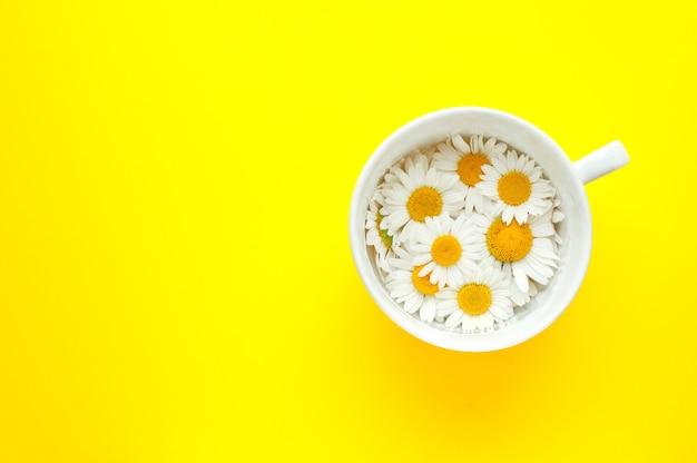 Чашка чая с цветами ромашки на желтой поверхности