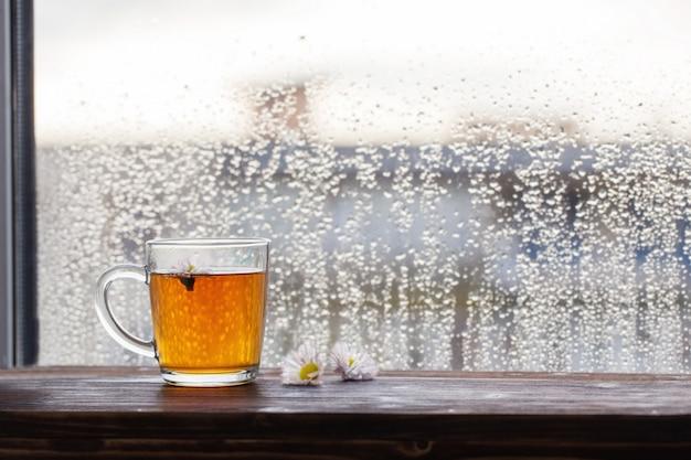 夕暮れ時の雨滴を持つウィンドウのカモミールの花とお茶のカップ