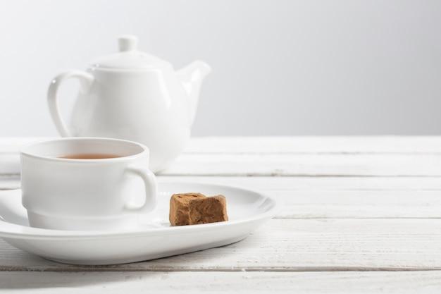 Чашка чая с шоколадной конфетой на деревянный стол