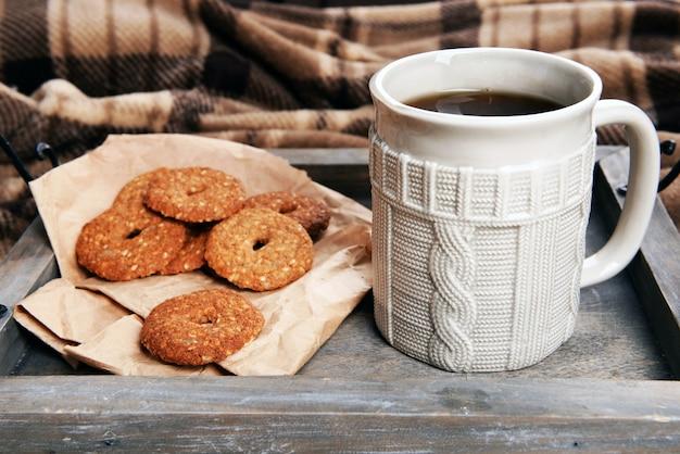 テーブルのクローズアップにクッキーとお茶のカップ