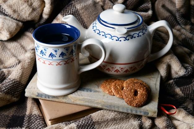Чашка чая с печеньем на столе крупным планом
