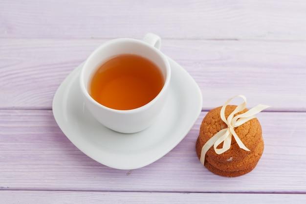 ライラックの木の背景にクッキーとお茶のカップ