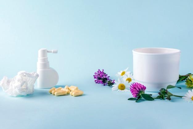 꽃 카모마일과 꽃이 만발한 샐리와 알약을 넣은 차 한잔, 콧물과 목에 스프레이. 계절성 질병 및 감기, 독감, 더위 치료. 한약재 vs 한약재.