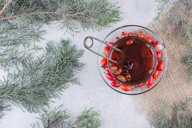 Чашка чая со свежими плодами шиповника на мраморном столе. фото высокого качества