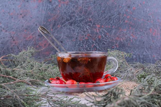 大理石のテーブルに新鮮なローズヒップとお茶のカップ。高品質の写真