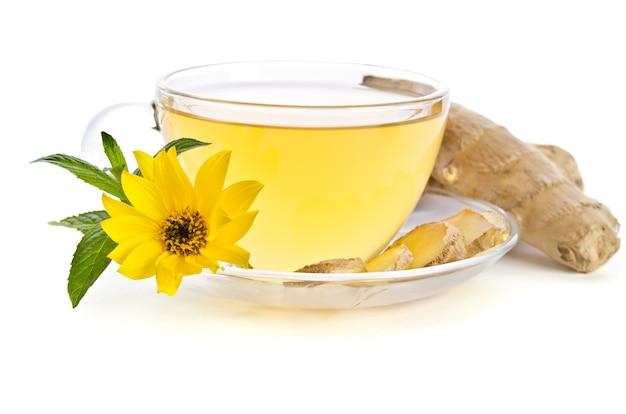 生姜のスライスとエキナセアの花が白で隔離された近くのお茶のカップ