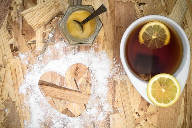木製のテーブルの上のハートの形とお茶のカップ
