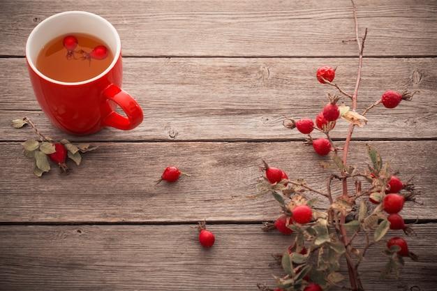 ヒップのバラ、木製のテーブルとお茶のカップ