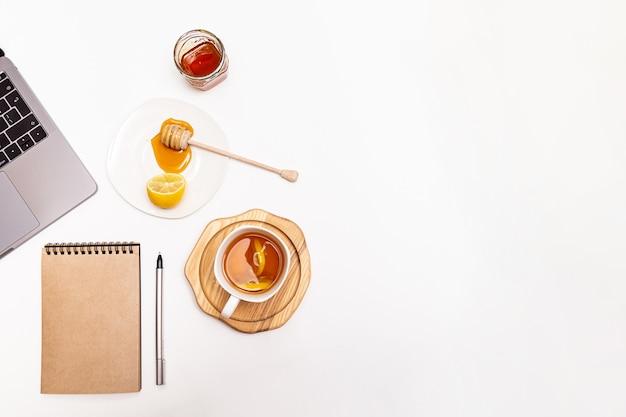 蜂蜜とレモンとお茶のカップラップトップとペンでノート