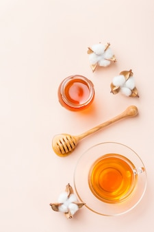 Чашка чая с медом на модном пастельно-розовом абрикосовом фоне. копирование пространства, плоская планировка