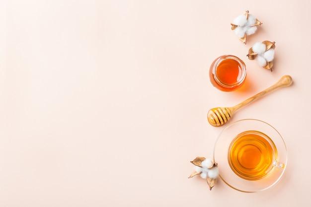トレンディなパステルピンク、アプリコットの背景に蜂蜜とお茶のカップ。コピースペース、フラットレイ