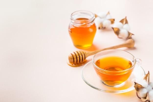 Чашка чая с медом на модном пастельно-розовом абрикосовом фоне. копировать пространство