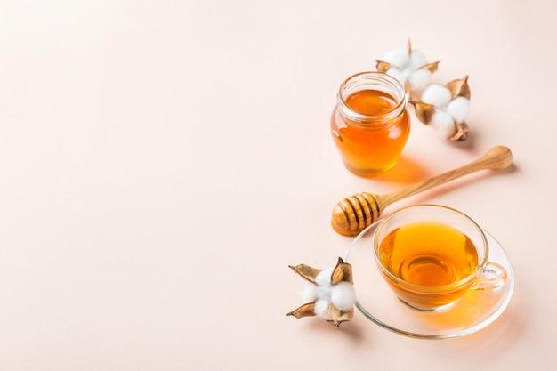トレンディなパステルピンク、アプリコットの背景に蜂蜜とお茶のカップ。コピースペース