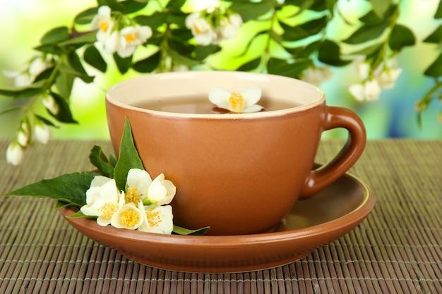 明るい背景に、竹マットの上に、ジャスミンとお茶のカップ