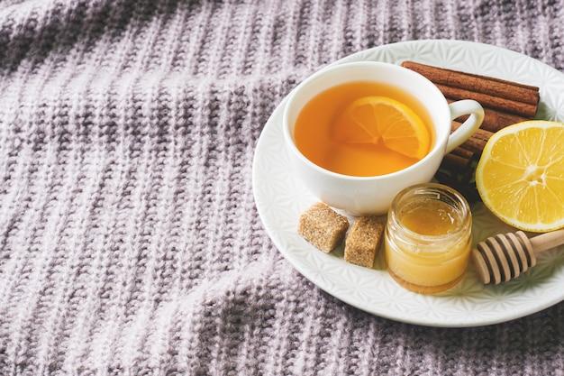 Чашка чая с лимоном и печеньем, медом и палочками корицы, аниса на одеяле