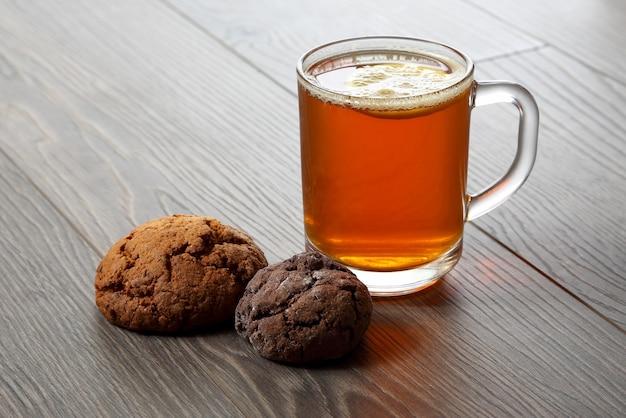 Чашка чая с лимоном и печеньем на деревянном столе