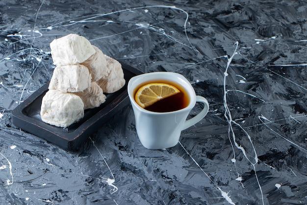 大理石の表面にレモンと綿菓子のプレートとお茶のカップ。