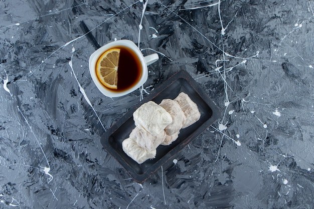 대리석 표면에 레몬과 솜사탕 접시를 넣은 차 한 잔.