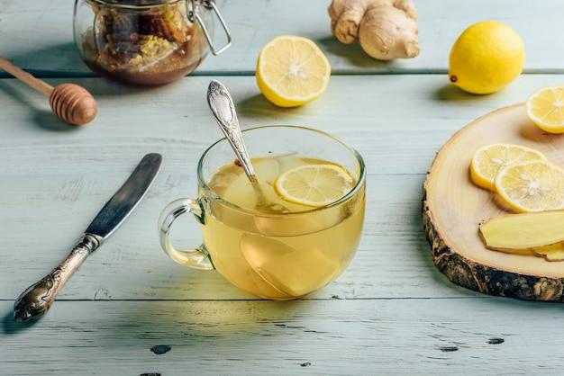 Чашка чая с лимоном, медом и имбирем на деревянной поверхности