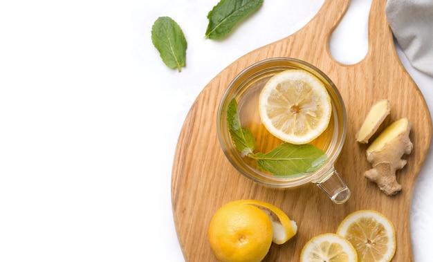 Чашка чая с лимоном, мятой и имбирем крупным планом на белом