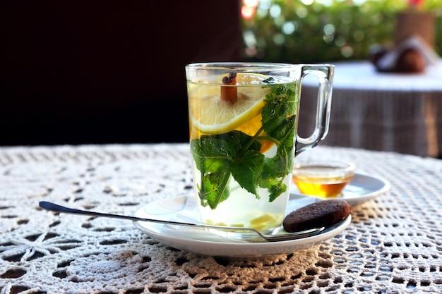 Чашка чая с лимоном, мятой, корицей и десертом