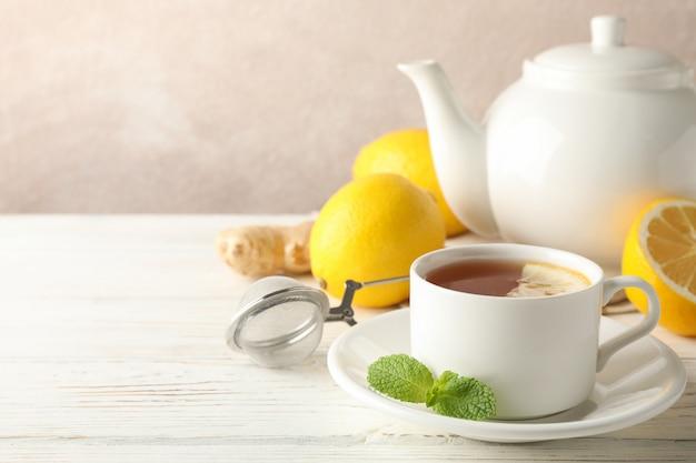 レモン、ミント、ストレーナー、ジンジャー、木製のコピースペースにティーポットとお茶のカップ