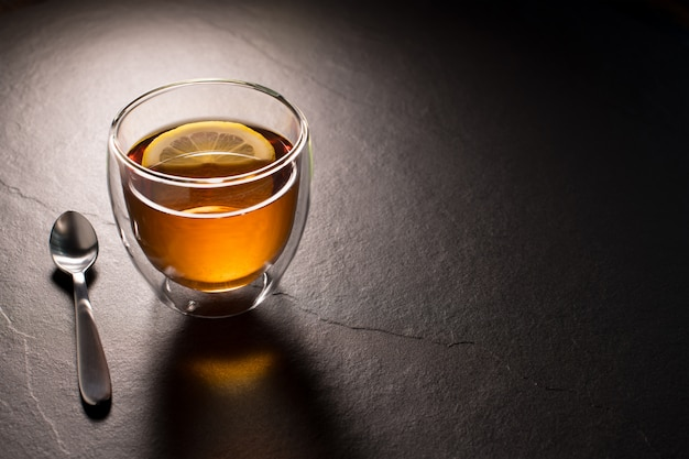 黒御影石の背景にレモンとお茶のカップ