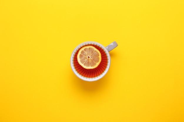 Чашка чая с лимоном на желтом фоне. вид сверху, плоская планировка. скопируйте пространство. чай на осень или зиму.