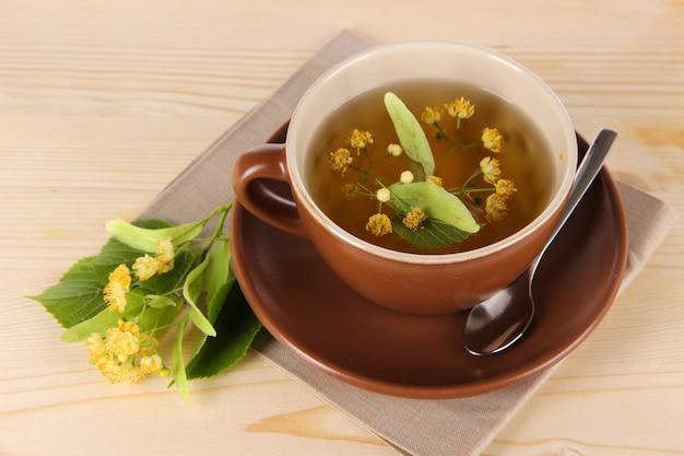 Чашка чая с липой на салфетке на деревянном столе