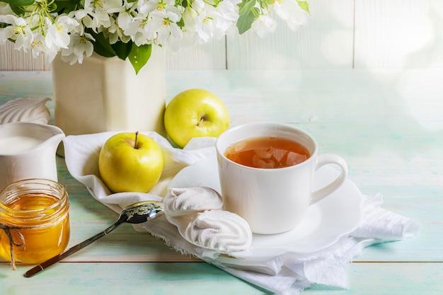Чашка чая с зефирами, медом и яблоками и ветвями цветения яблони в вазе на деревянном столе с bokeh.