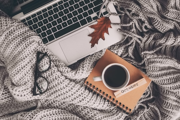 ノートブック、ラップトップ、編み物服とお茶のカップ。