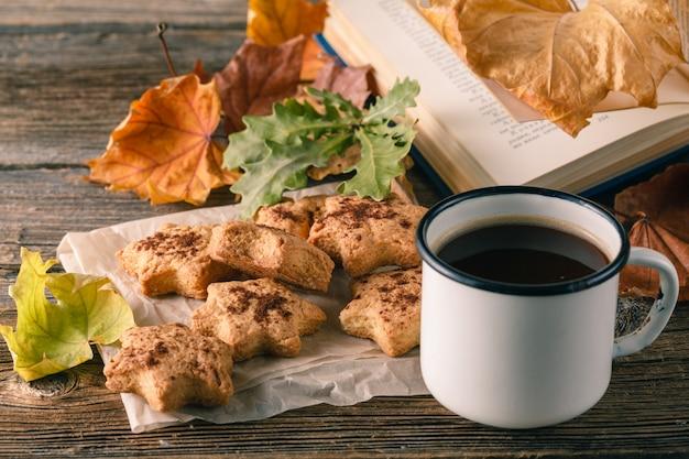 Чашка чая с старой книги, осенние листья на деревянный стол.