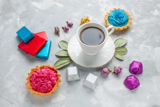 ライトデスクにピンクのクリームケーキチョコレートキャンディー、ビスケットスウィートティーキャンディーとお茶のカップ