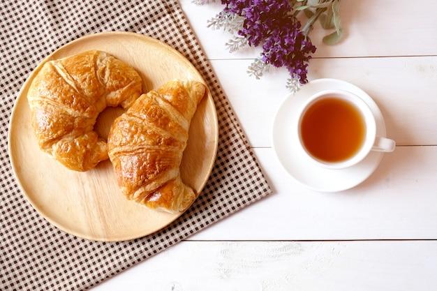 紫色の花と白い木製の背景にクロワッサンと木製皿とお茶のカップ。