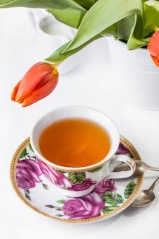 白で赤いチューリップとお茶のカップ