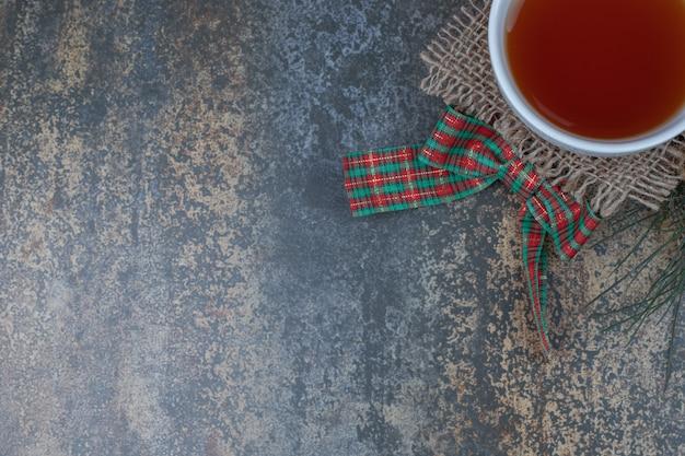 大理石のテーブルにリボンとお茶のカップ。高品質の写真